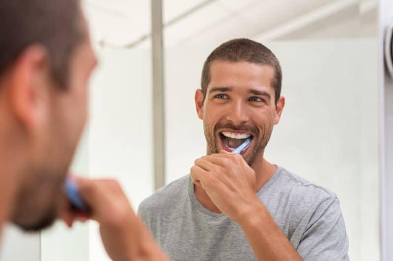 Happy man brushing teeth